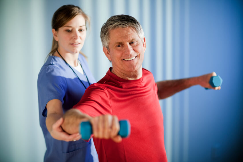 Middle-aged man lifts dumbbells with the assistance of a young physical therapist. Vignetting on the corners. Horizontal shot.