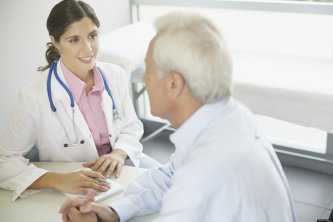 Doctor sitting in office with patient talking and smiling