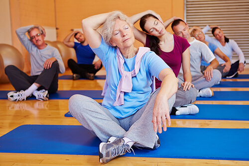 Gruppe macht Dehnübungen beim Rückentraining im Fitnesscenter